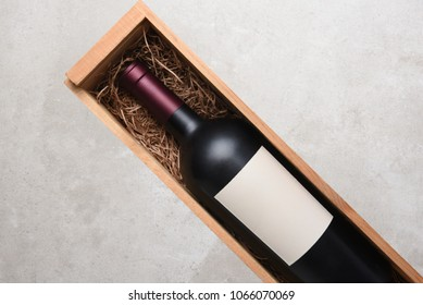 Red Wine Bottle: A single bottle of Cabernet wine in a wood case with packing straw. Bottle is at an angle with copy space on both sides.