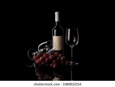 Red wine bottle and twi glasses with grape on black background