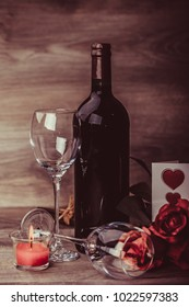 Red wine bottle, two glasses of wine, roses with love message on wooden table. Valentines day celebration concept. Copy space.