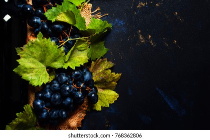 Red wine in bottle, vine and grapes, black blue background, top view