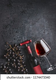 Red wine bottle with vintage corkscrew, glass and grapes on retro black background, top view.