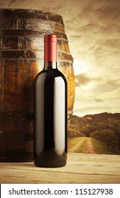 red wine bottle and wodden barrel, vineyard on background