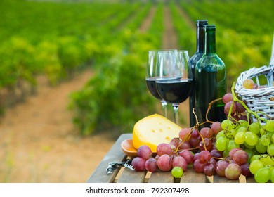 Red wine bottles and glasses on wooden table with cheese and grapes overlooking vineyard