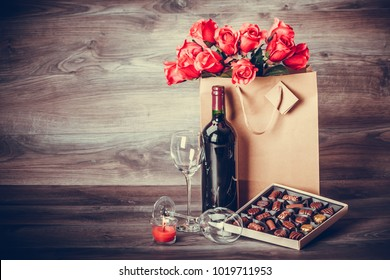 Red wine bottle,two glasses of wine, box of chocolates and roses in a paper bag on wooden table. Valentines day celebration concept. Copy space.