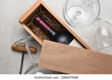 Red Wine Box: A single bottle of Cabernet in a wood box partially covered by its lid with empty glasses and a corkscrew