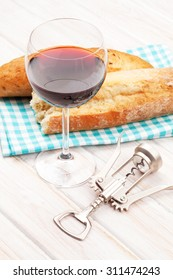 Red wine and bread on white wooden table