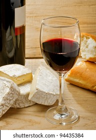 Red wine, Brie, Camembert and bread on the wood surface, studio shot