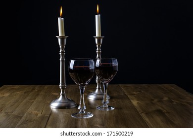 Red Wine with candles on wood table