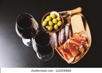 Red wine with charcuterie, cheese and olives on wooden board