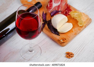 Red wine, cheese, basil and prosciutto on white wooden background