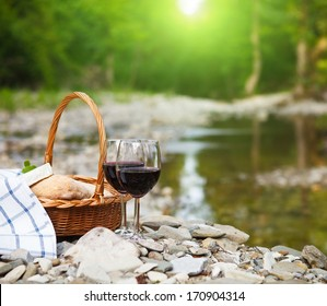 Red wine, cheese and bread served at a picnic. Mountain river background