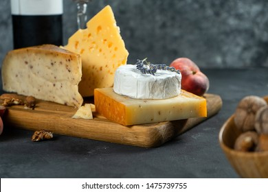 Red wine and cheese. Different types of cheese with nuts, lavander and fig peach on cutting board. Romantic dinner. Copy space for design. Dark background. Soft focus