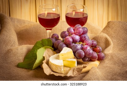 Red wine with cheese and grapes on sackcloth on a background of a wooden wall and autumn leaves. For this photo applied vignetting effect.