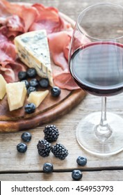 Red wine with cheese, ham and berries