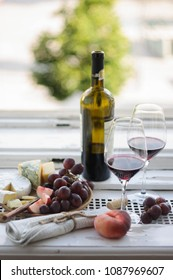 Red wine and cheese platter on a rustic window sill