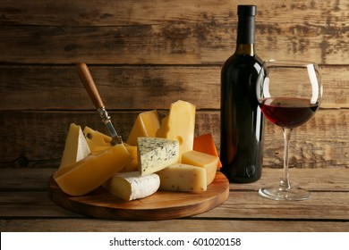 Red wine and cheeseboard on wooden background