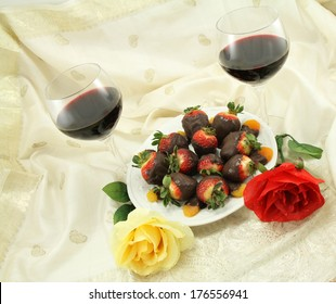 Red wine with chocolate covered strawberries, chocolate covered apricots and rose