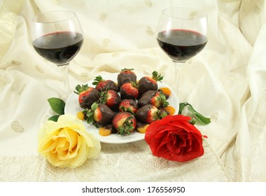 Red wine with chocolate covered strawberries, chocolate covered apricots and roses.