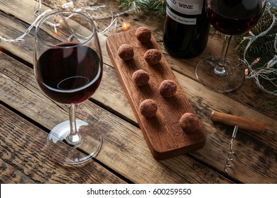 Red wine, chocolate dessert and Christmas decorations on wooden table