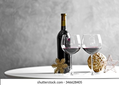 Red wine and Christmas ornaments on wooden table on wall background