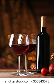 Red wine and Christmas ornaments on wooden table on wooden background