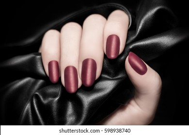 Red wine color manicure. Black silk or leather background.