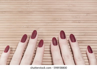 Red wine color manicure. Wooden table background
