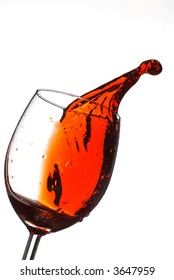 Red wine coming out from glass with bright background
