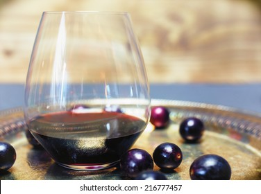 Red wine in crystal stemless glass with Muscadine grapes on silver platter.
