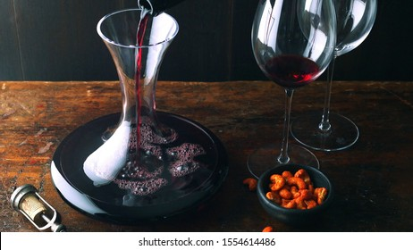 Red wine is decanted into decanter next to cashew nuts on rustic wooden table