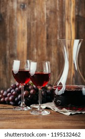 Red wine, decanter, two glasses and dark grapes on a wooden background