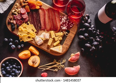 Red wine with different kinds of cheese, charcuterie assortment, crackers, grapes, nuts and berries on the dark concrete background