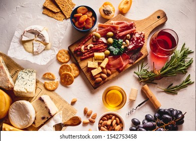Red wine with different kinds of cheese, charcuterie assortment, crackers, grapes, nuts and berries on the white concrete background