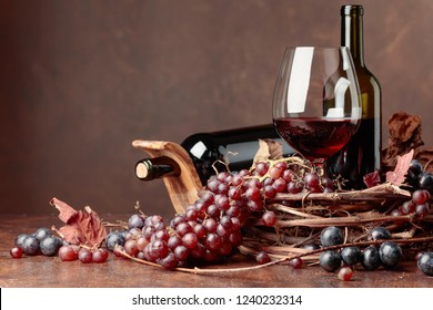 Red wine and fresh grapes with dried up vine leaves, copy space for your text.