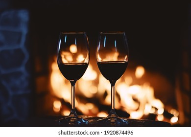 Red wine in front of a fireplace, relaxing atmosphere at home