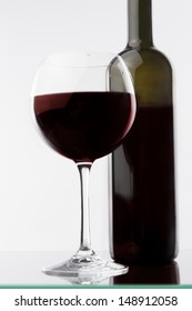 red wine glass and bottle against white background