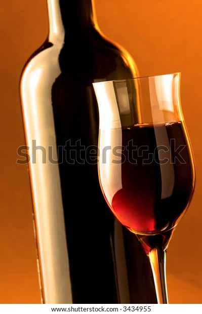Red wine. Wine glass and wine bottle details.Warm background light.
