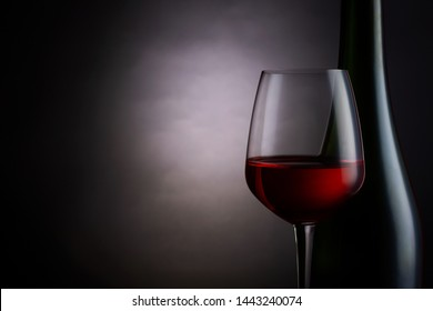 Red wine in a glass with wine bottle on dark background.