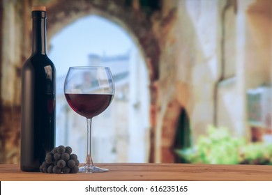 Red wine glass and red wine bottle on the winery backgroung