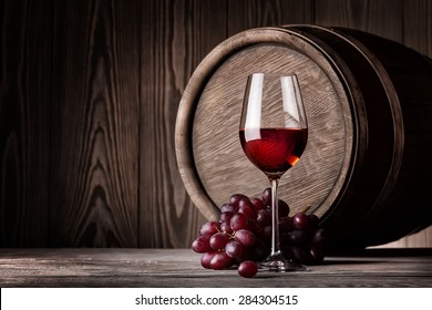 Red wine in glass and bunch of grapes on background of wooden barrels