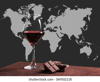 Red wine glass with chocolate and world map