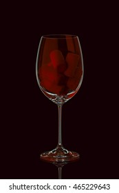 Red Wine Glass with corks inside isolated on black background. Coyspace. Toned