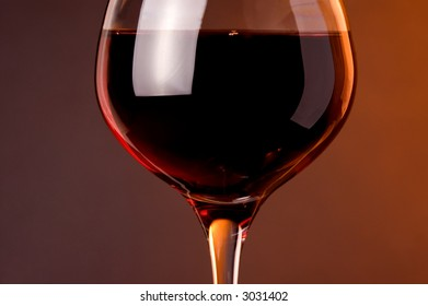Red wine. Wine glass detail with red wine. Warm color background.