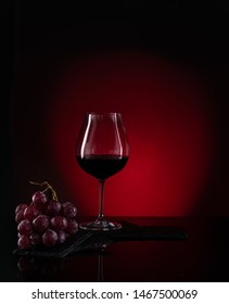 Red wine in glass with grapes in dark