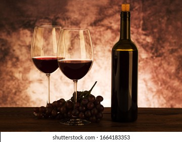 Red wine. Glass of red wine, grapes and decanter on wooden background.