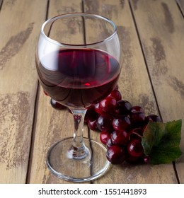 red wine in a glass with grapes on the boards