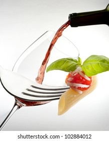 red wine glass with macaroni on white background