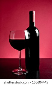 red wine glass near bottle on red background and wood table