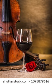 Red wine in glass and old, classical violin
