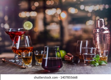 Red wine in a glass on a bar counter. Assortment of different strong alcohol drinks over night lights background. Copy space